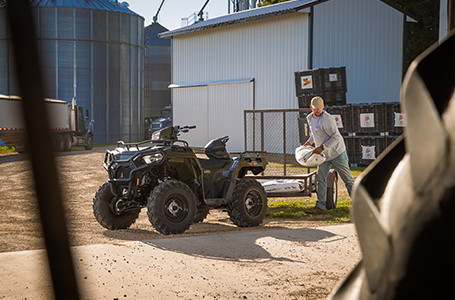A farmer loading materials to his Sportsman 570