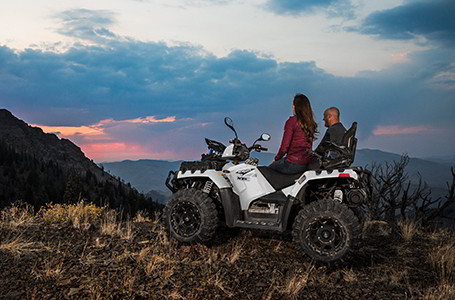 Two Sportsman Touring XP 1000 sitting on their vehicle watching the sunset