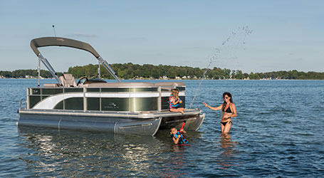 Family swimming and playing in the water near their Bennington pontoon boat