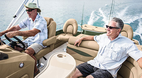 Bennington owner driving his pontoon boat, while a boater relaxes in the passenger seat