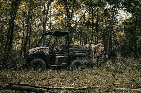 Two hunters and a Ranger EV in the woods